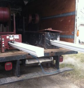Seamless gutters being made in the back of a company truck.